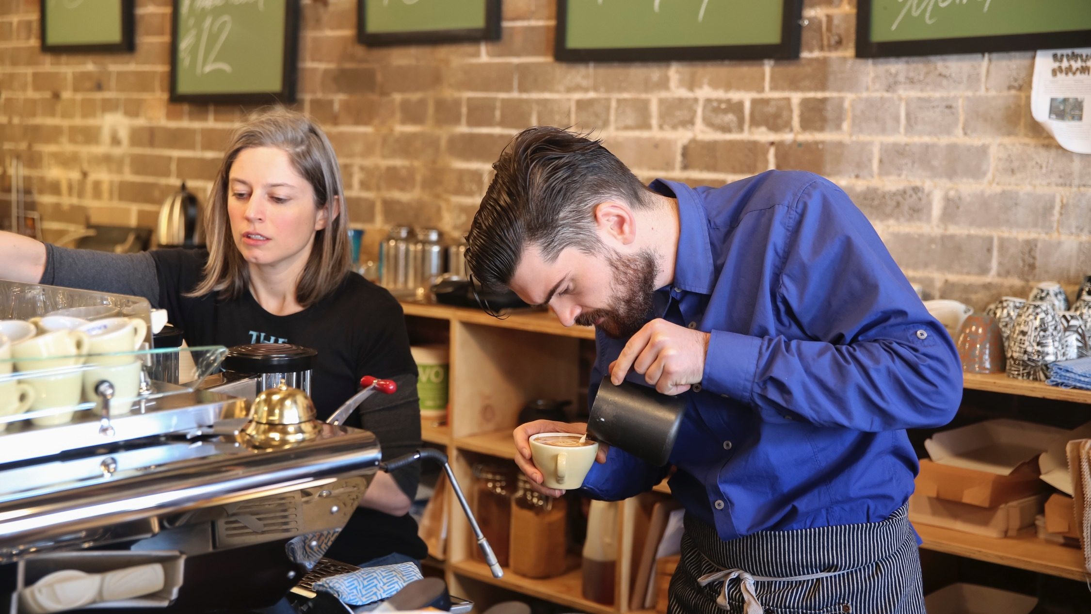 A barista pouring a coffee