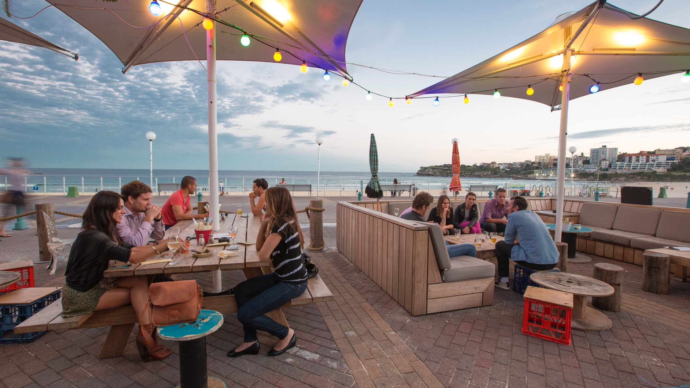 Customers sitting in the outdoor area with a view of Bondi Beach