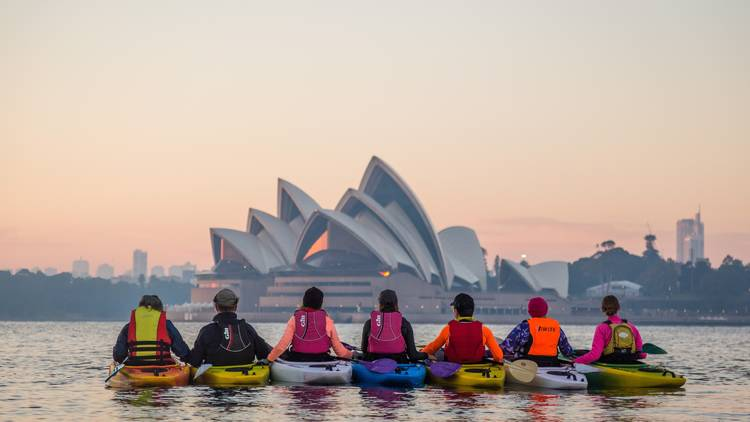 Sunrise tour of kayakers in front of Sydney Opera House