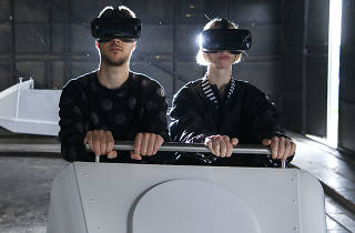 Two people sat in a ghost train carriage with virtual reality headsets