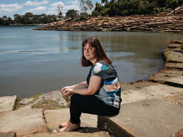 Emily McDaniel sitting at Nawi Cove, Barangaroo