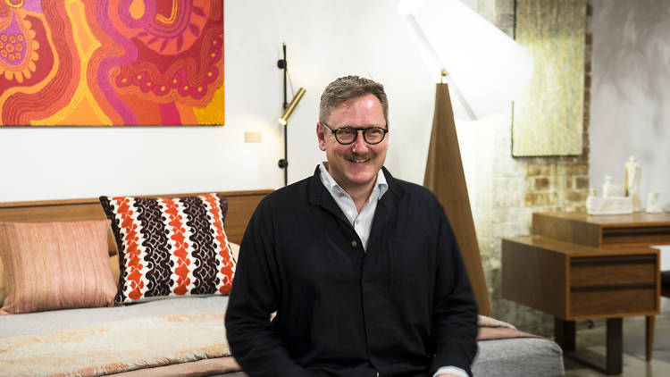 Ross Longmuir sat on a bed at his furniture store