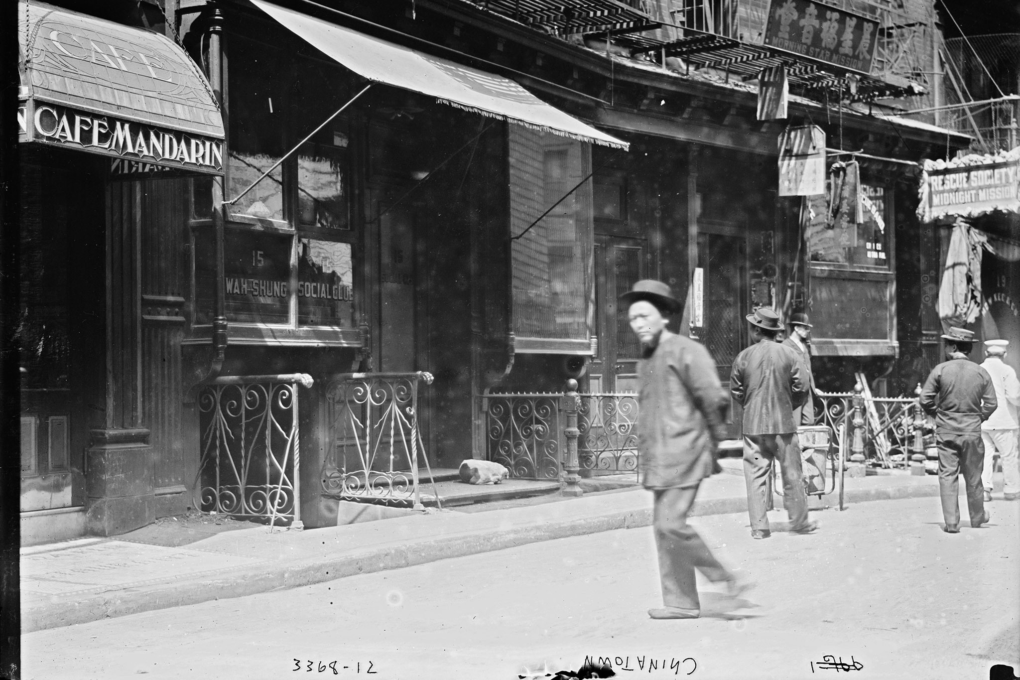 Photograph shows street scene in front of Cafe Mandarin, 11-13 Doyers Street, Chinatown, New York City.