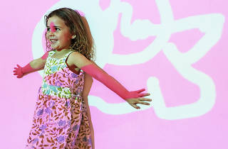Child standing against a pink wall with projection