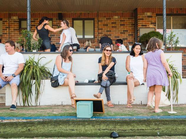 People sitting outside on the green at Bondi Bowling Club