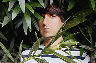 Comedian Demetri Martin hiding in the brush