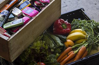 Crate of mobile phones, crate of fresh fruit and vegetables