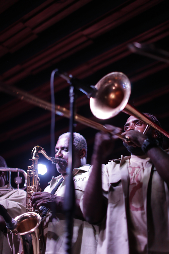 Musicians play brass instruments on a dark stage