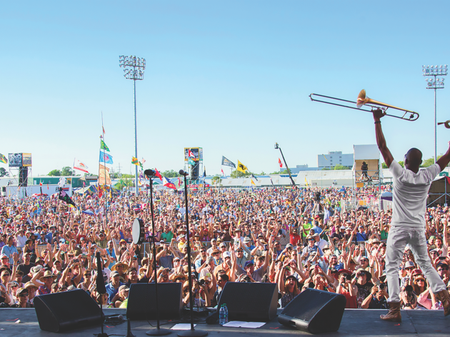 A large crowd cheers for a trumpet player at a festival in Louisiana
