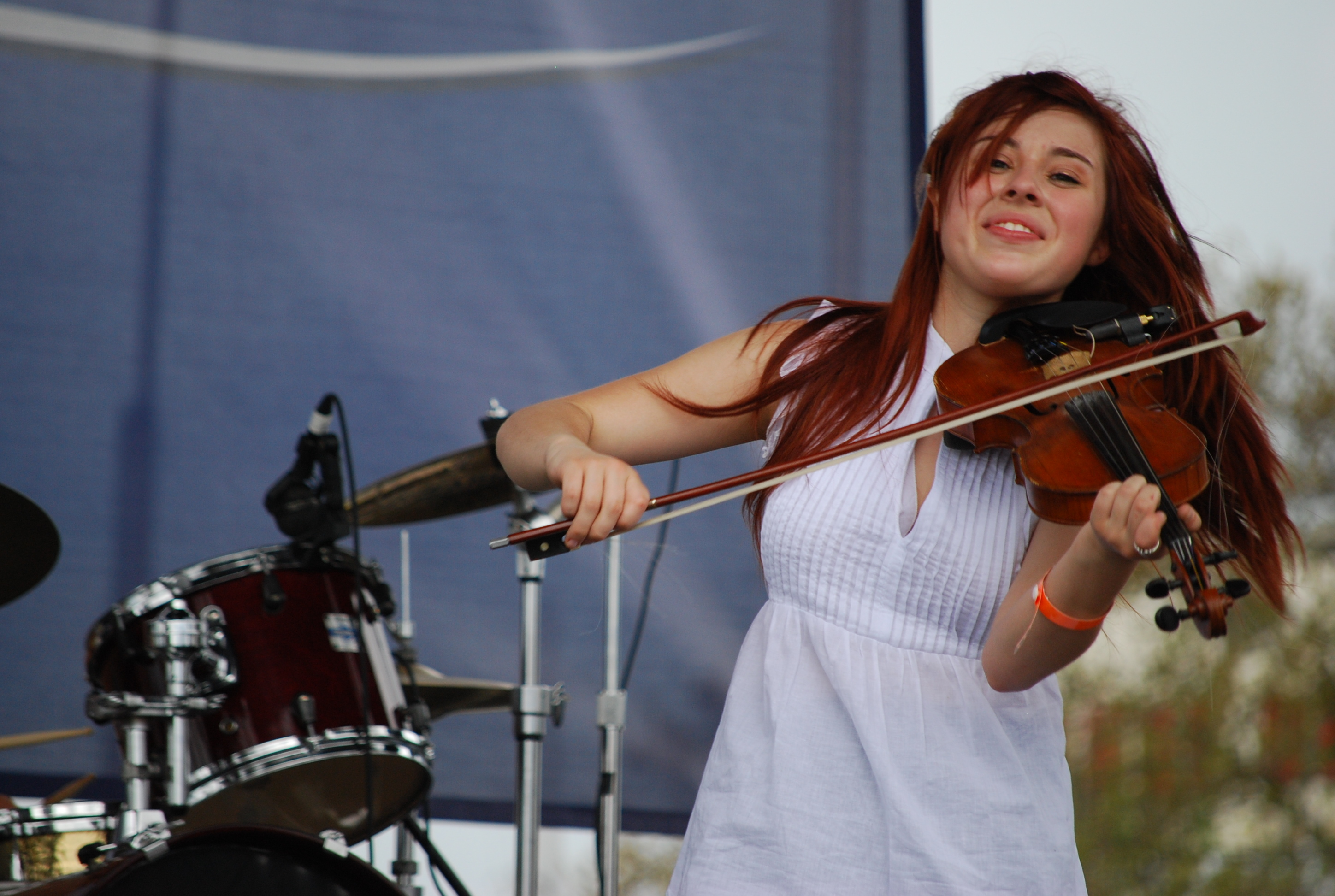 A woman plays violin at an outdoor festival
