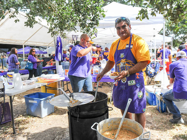 A man in a bright purple LSU apron cooks from a giant cauldron