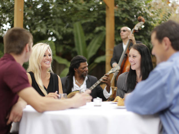 Four people sit at a white table-cloth clad outdoor table, watching two jazz musicians