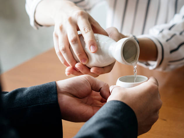 Hands pouring sake into a sake cup