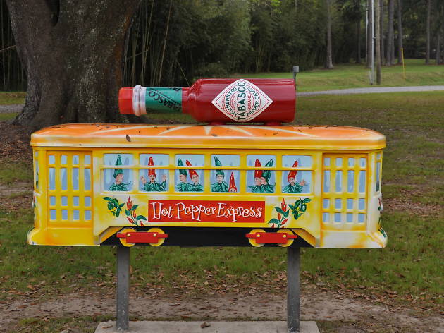A yellow 'hot pepper express' train carriage on a pole, with a bottle of Tabasco on top of it
