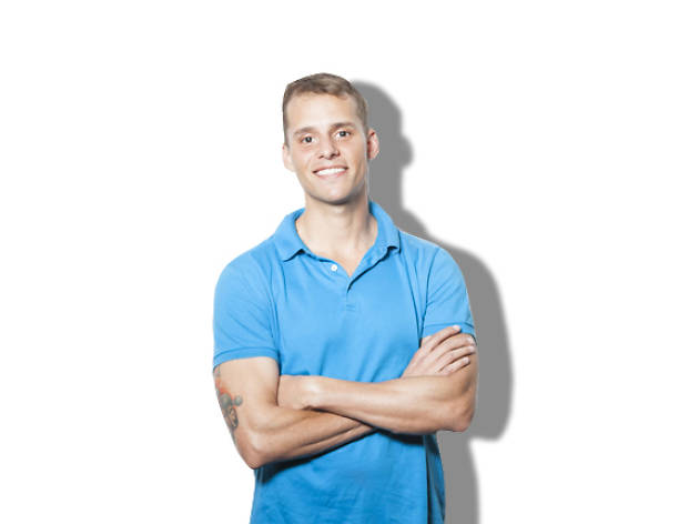 Corey stands with his arms folded against a white backdrop
