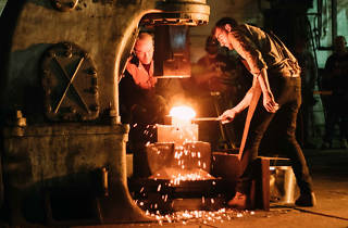 A man forges metal at a furnace