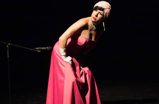 Performer in a ball gown mimes farting into a microphone