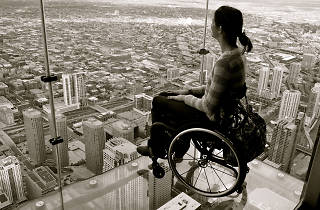 Woman in a wheelchair looking out of a high rise building