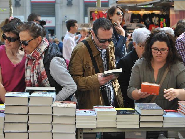 Gent mirant llibres a la parades de carrer la diada de Sant Jordi 2017