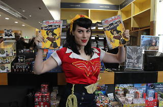 Cosplayer poses with comic books.