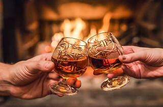 Hands toasting with whiskey in front of fireplace