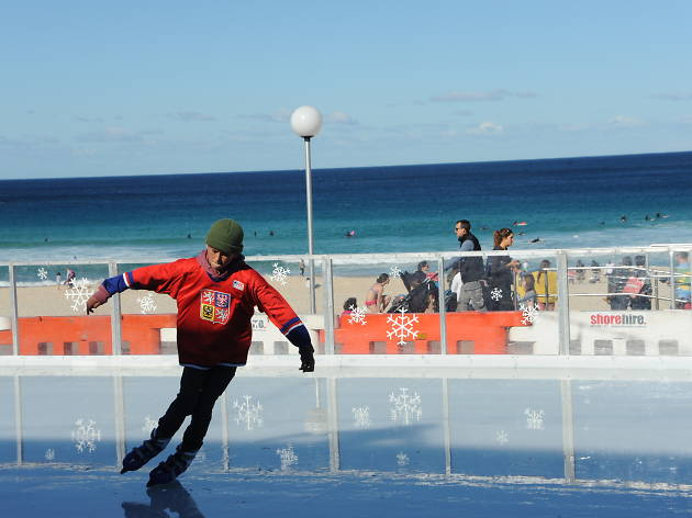Boy skates on beachside ice rink.