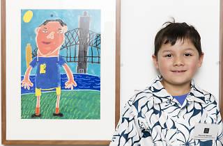 Boy stands next to winning artwork.
