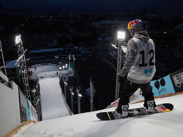Snowboarder stands at top of ski ramp.