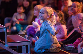 Kids watch a stage performance.