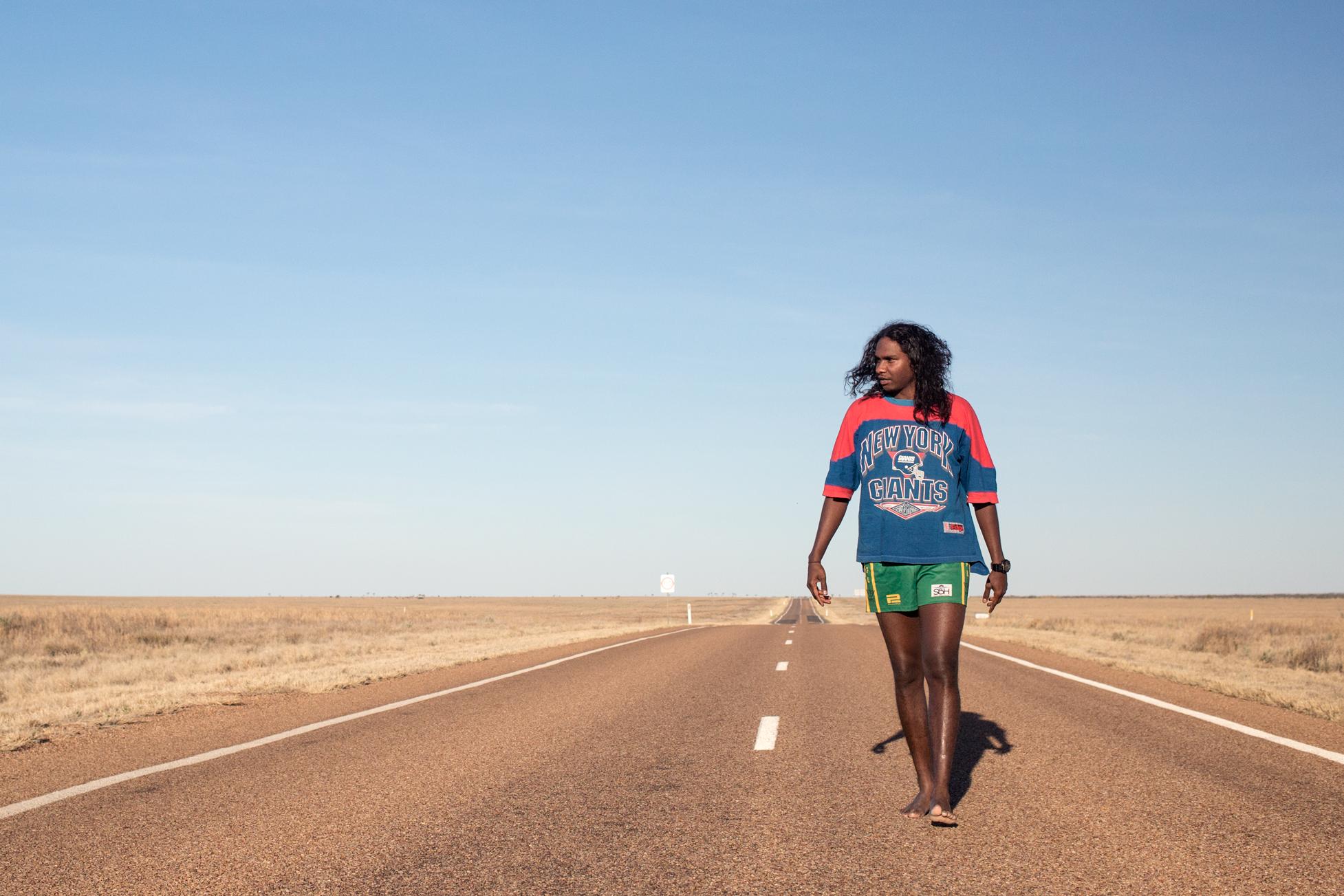 Baker Boy walking on a road in the desert