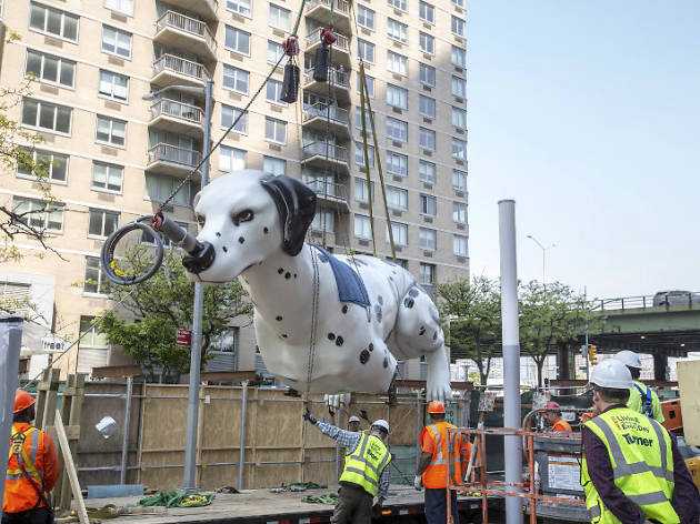 A 38-foot statue of a dog balancing a taxi on its nose was unveiled in midtown