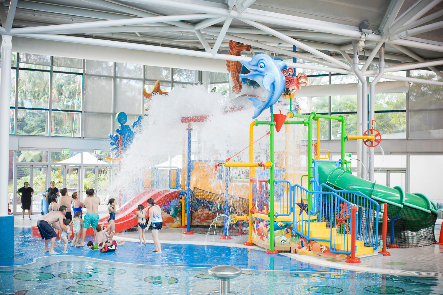 A large water slide indoors with families playing in the water