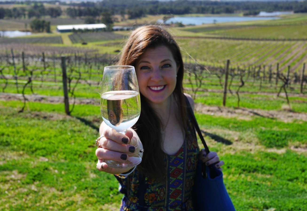 Woman holds glass of white wine in a vineyard.