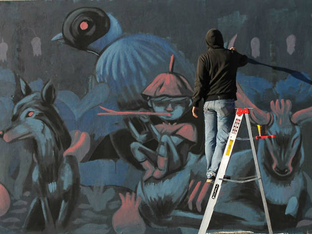 Muralista pintando en una pared