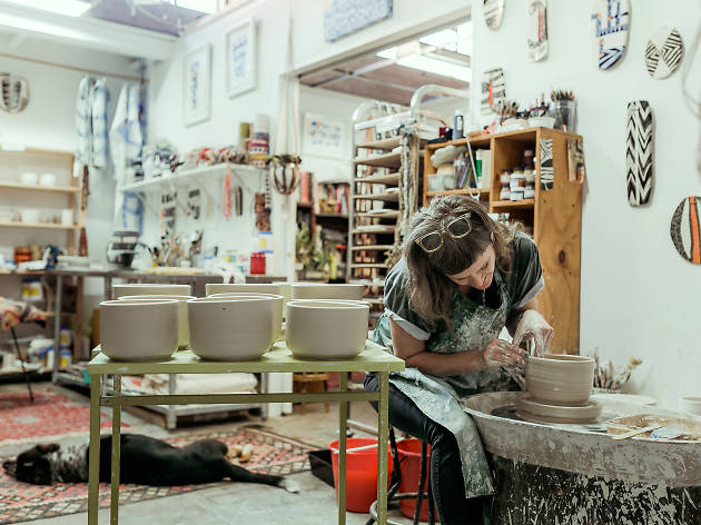 Woman sculpts clay in busy studio.