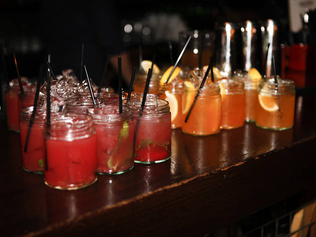 Cocktails lined up in jam jars.
