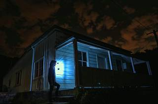 Person holds light at haunted house.