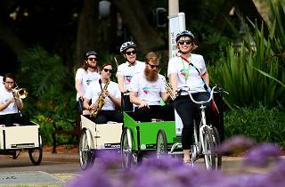 people ride in carts at Hyde Park for the Cargo Bike Parade.