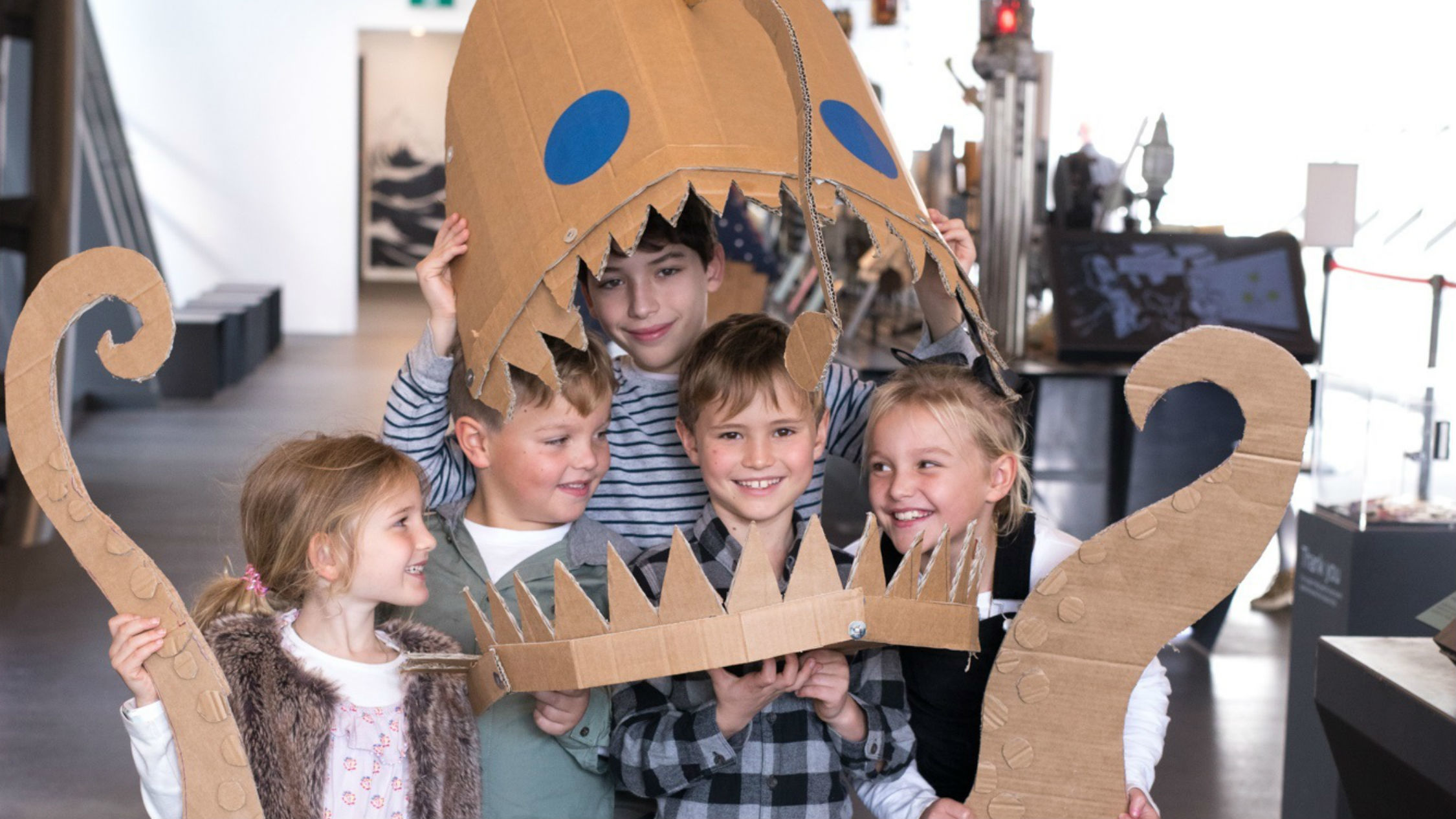 Kids pose with their craft sea creature project.