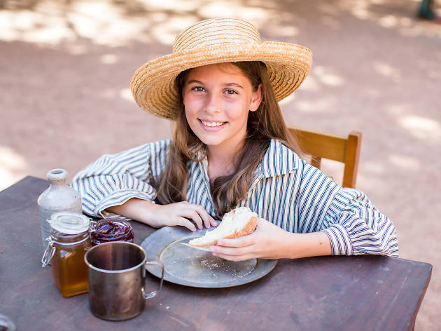Girl sits eating bread dressed as a convict.