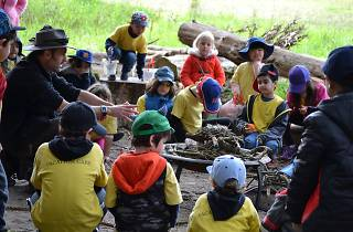 Children and rangers sit around a campfire.