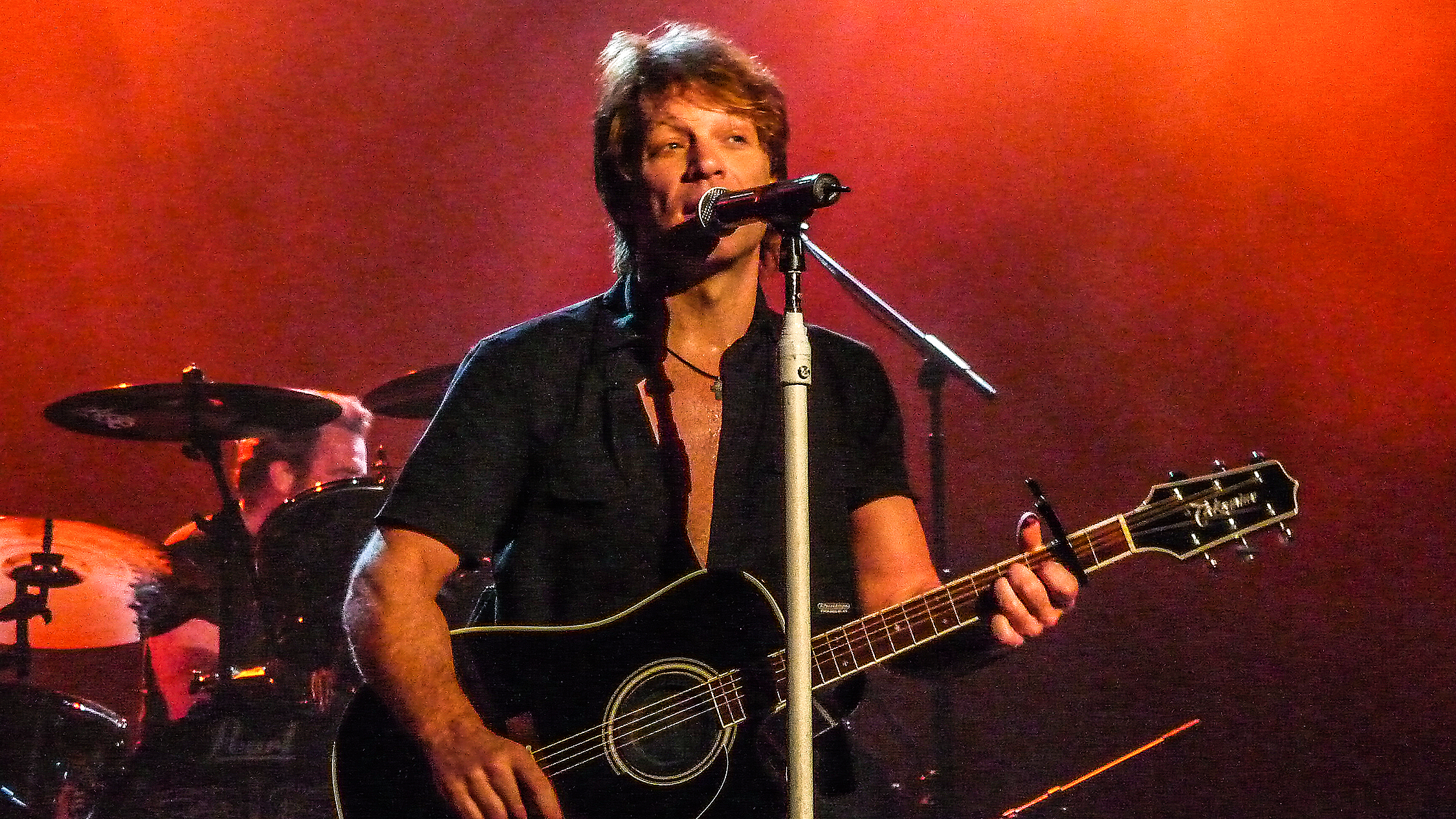 Musician Jon Bon Jovi in concert on stage holding a guitar