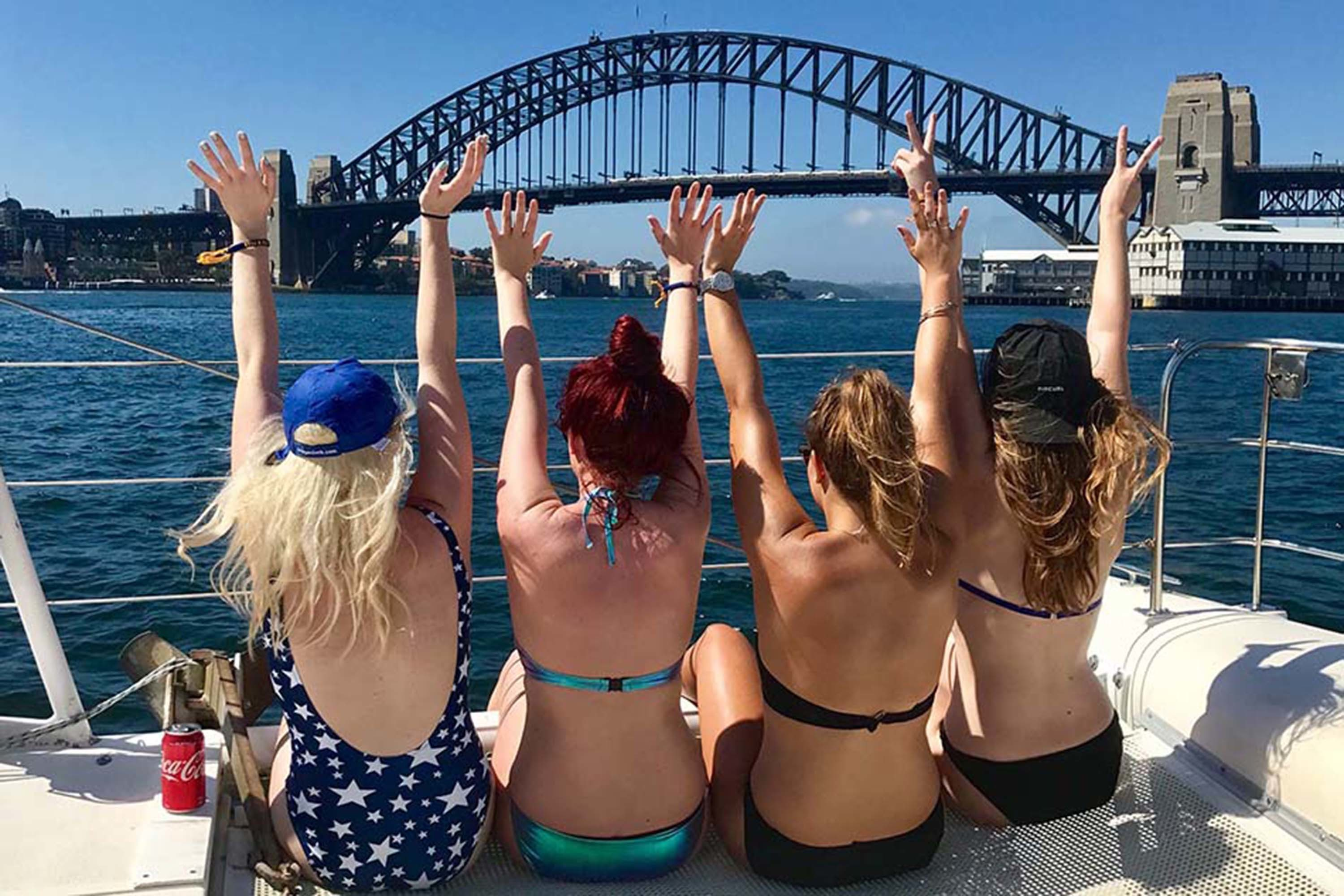 Women with their hands in the air, looking at Sydney Harbour Bridge
