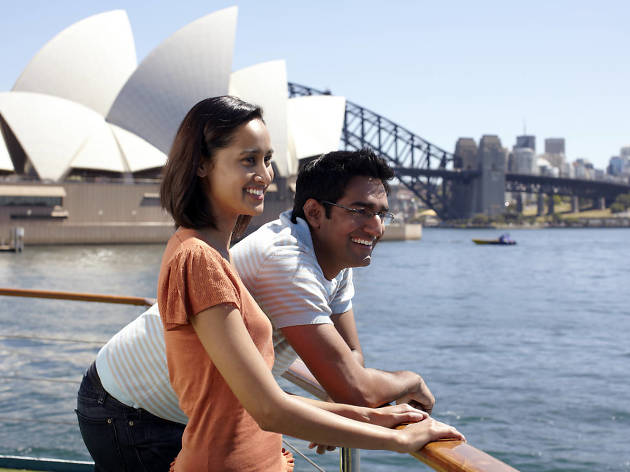Two people on a boat in front of Sydney Opera House and Bridge