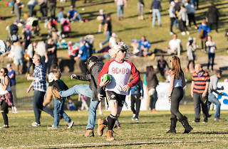 A man in a wig and ACDC short running on a football field