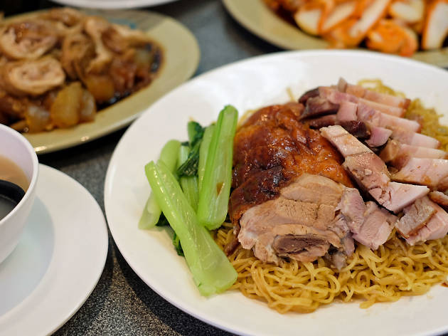 A plate of roast meats on noodles