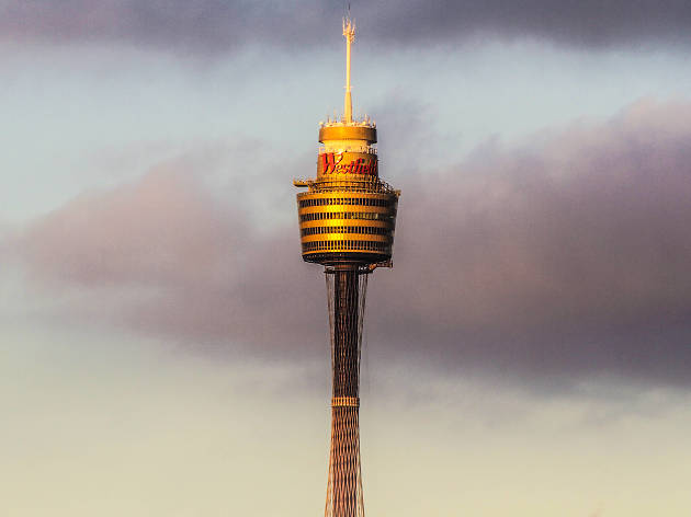 Top half of Sydney Tower against a pale sky with dark clouds