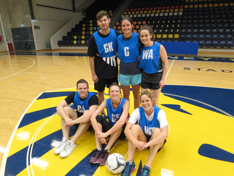 Team poses wearing netball bibs.