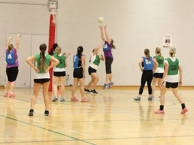 People play netball in green bibs.