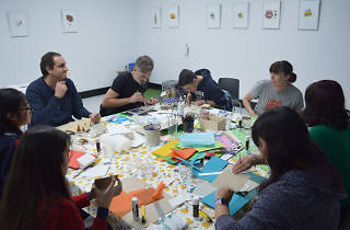 People sit at a table with craft items.